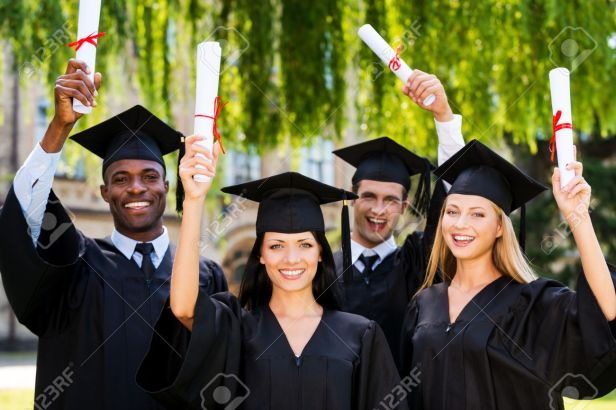 Happy graduates. Four college graduates showing their diplomas and smiling while standing close to each other and